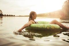 Jovem mulher que relaxa na água em um dia de verão Fotografia de Stock Royalty Free