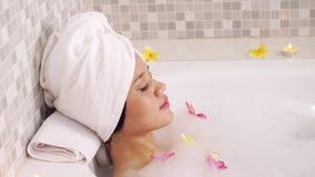 Jovem mulher que relaxa na banheira video estoque