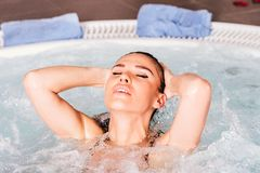 Jovem mulher que relaxa na banheira de hidromassagem Imagens de Stock