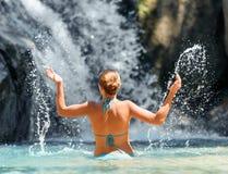 Jovem mulher que relaxa na cachoeira Fotos de Stock Royalty Free