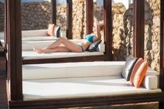 Jovem mulher que relaxa na cadeira de plataforma pela piscina no recurso imagens de stock