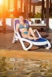 Jovem mulher que relaxa na cadeira de plataforma pela piscina no recurso Alargamento de Sun imagem de stock