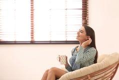 Jovem mulher que relaxa na cadeira papasan perto da janela com cortinas em casa fotos de stock