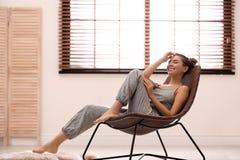 Jovem mulher que relaxa na cadeira perto da janela com cortinas em casa imagem de stock