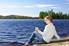 Jovem mulher que relaxa na costa do lago Imagens de Stock