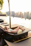 Jovem mulher que relaxa na piscina do telhado em Singapura imagens de stock royalty free