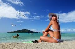 Jovem mulher que relaxa na praia que aprecia os pássaros de vôo contra as ilhas verdes Fotografia de Stock Royalty Free