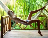 Jovem mulher que relaxa na rede em um recurso tropical foto de stock royalty free