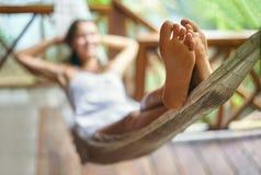 Jovem mulher que relaxa na rede em um recurso tropical Foco em f imagens de stock