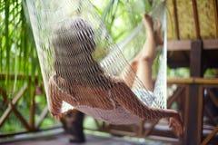 Jovem mulher que relaxa na rede em um recurso tropical Vista traseira imagem de stock