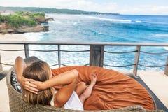 Jovem mulher que relaxa na sala de estar na varanda com opinião do mar fotografia de stock royalty free