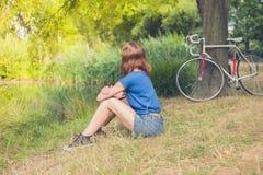 Jovem mulher que relaxa pela água no parque fotografia de stock