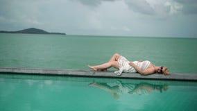 Jovem mulher que relaxa perto da associação video estoque