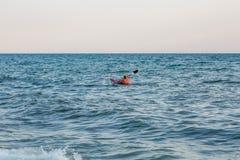 Jovem mulher que rema o caiaque do mar Férias ativas imagens de stock