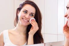 Jovem mulher que remove a composição no banheiro Fotografia de Stock Royalty Free