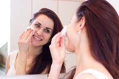 Jovem mulher que remove a composição no banheiro Imagens de Stock Royalty Free
