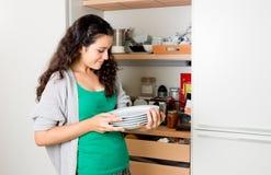 Jovem mulher que remove o dishware do armário para ajustar a tabela foto de stock royalty free