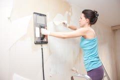 Jovem mulher que remove o papel de parede fotografia de stock
