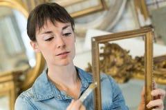 Jovem mulher que renova a moldura para retrato antiga imagens de stock