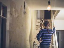 Jovem mulher que renova uma escadaria imagens de stock