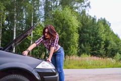 Jovem mulher que repara seu carro imagens de stock royalty free