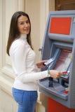 Jovem mulher que retira o dinheiro do cartão de crédito no ATM imagem de stock