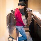 Jovem mulher que reza em uma igreja Imagem de Stock Royalty Free