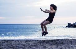 A jovem mulher que salta altamente na praia, dando certo Fotografia de Stock Royalty Free