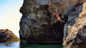 A jovem mulher que salta ao mar de um penhasco Foto de Stock Royalty Free