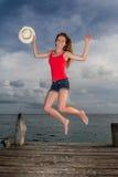 A jovem mulher que salta no cais Imagens de Stock Royalty Free