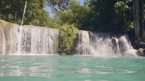 A jovem mulher que salta no lago da cachoeira da corda e para colar o movimento lento Mulher alegre que salta da corda na água az filme