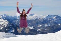 A jovem mulher que salta para a alegria e a felicidade nas montanhas Foto de Stock Royalty Free