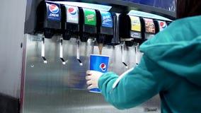 Jovem mulher que seleciona a bebida fresca da fonte da máquina da soda do serviço do auto filme