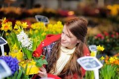 Jovem mulher que seleciona flores frescas no mercado Imagens de Stock Royalty Free