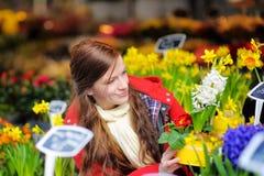 Jovem mulher que seleciona flores frescas no mercado Foto de Stock