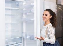 Jovem mulher que seleciona o refrigerador doméstico no supermercado imagem de stock