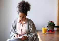 Jovem mulher que senta em casa a escrita na almofada de nota Fotos de Stock