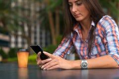 Jovem mulher que senta mensagens fora de leitura e de datilografia em seu smartphone Imagem de Stock Royalty Free
