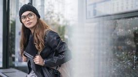 Jovem mulher que senta a parada do ônibus fotos de stock royalty free