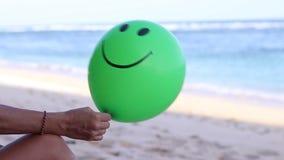 Jovem mulher que senta-se alegremente na praia com balão verde Bali, Indonésia HD completo, 50fps vídeos de arquivo