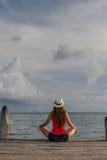 Jovem mulher que senta-se com pés cruzados e que aprecia o por do sol no mar Fotos de Stock Royalty Free
