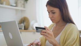 Jovem mulher que senta-se com portátil em casa, pagando por compras com cartão de crédito video estoque