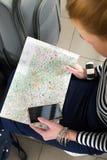 A jovem mulher que senta-se com uma tabuleta e está olhando o mapa Close-up recolhido em uma viagem Foto de Stock