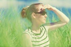 Jovem mulher que senta-se em dunas de areia entre o relaxamento alto da grama, apreciando a vista no dia ensolarado Imagens de Stock Royalty Free
