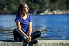 Jovem mulher que senta-se em rochas e para apreciar a vista no fiorde, Noruega fotografia de stock