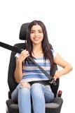 Jovem mulher que senta-se em um banco de carro Foto de Stock