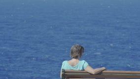 Jovem mulher que senta-se em um banco que negligencia o mar azul filme