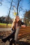 Jovem mulher que senta-se em um banco no parque da cidade no outono/inverno imagem de stock royalty free