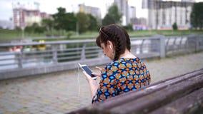 Jovem mulher que senta-se em um banco no parque e que escuta a música fotografia de stock royalty free