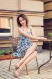 Jovem mulher que senta-se em um café da rua da cadeira de vime Sorri, olhar enviado à câmera Vestindo um vestido floral azul, cab fotografia de stock